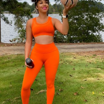 dr eva holding a basketball in orange workout clothes