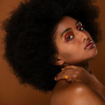 black curly afro hair on africal american woman posing in a brown background