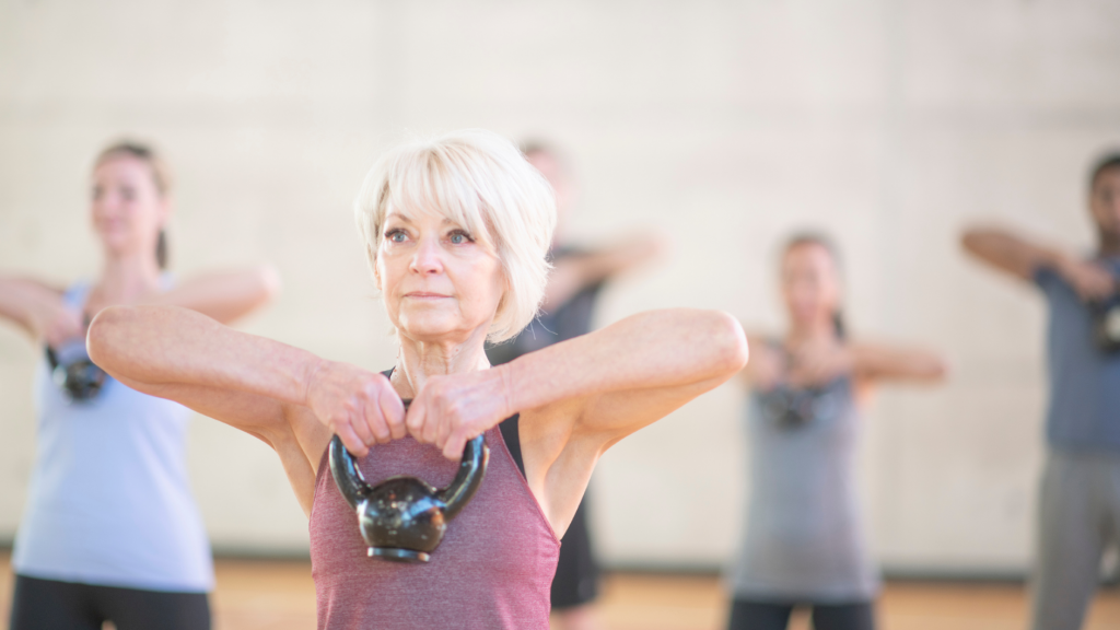 older woman in fitness class doing upright row