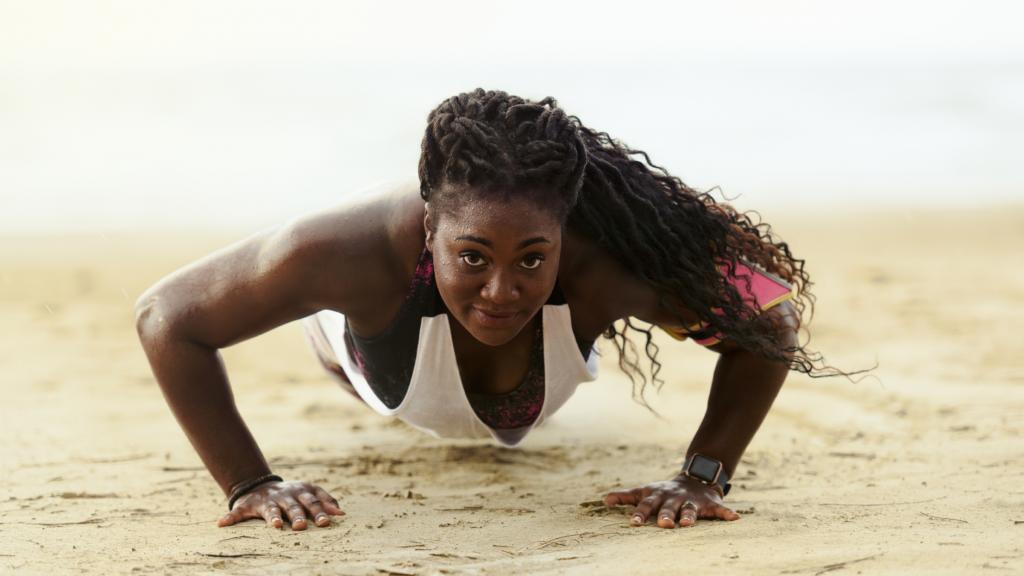 black woman doing push-ups on the beach